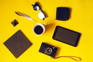 hot coffee, a tablet and a camera, a purse and glasses. notepad for writing. yellow background