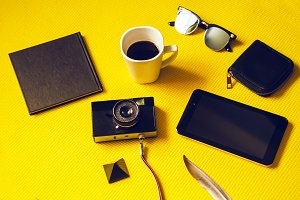 a camera on the road. notebook for writing, coffee cheer, wallet and tablet