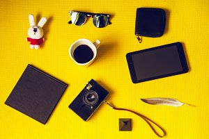 top view on a yellow background. fees for vacation. accessories for the road. photo camera, notebook, wallet, tablet, toy