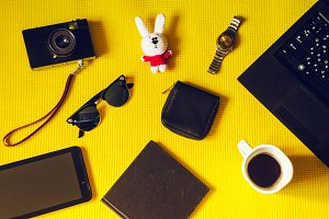 accessories for travel and adventure. view from above. yellow background. toy, laptop, camera, tablet, clock, coffee, notebook