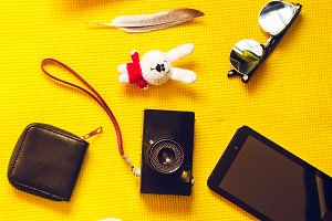 yellow background. view from above. camera, notepad empty, toy, glasses, tablet