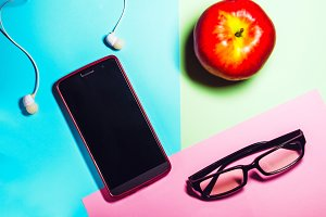 phone and glasses. working space. headphones for listening to music. technologies. food, red apple