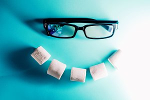 a smile from chewing marshmallow. smile for mood for the whole day. glasses like eyes.