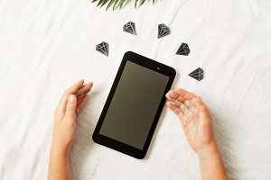 tablet in hands. view from above. diamonds against the background