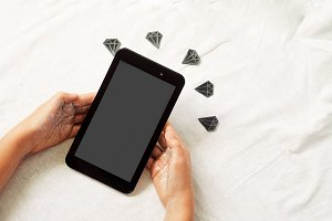 The hands hold the tablet. diamonds on the background.
