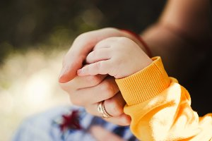 baby holds his mom's hand. support and care. motherhood