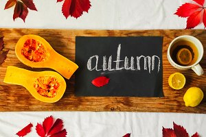 autumn background. the inscription on black paper chalk autumn. pumpkin, tea, lemons,