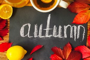 a beautiful chalk inscription on black paper the word autumn. hot tea. red leaves