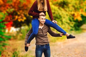 the guy is holding the girl on his shoulders. play on the street. autumn colorful day