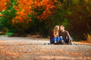 Couple admiring each other. sit on the blanket. travel and rest. Golden autumn
