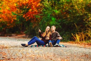 the couple is sitting on a blanket. walk in the street. autumn day. hot coffee. look somewhere