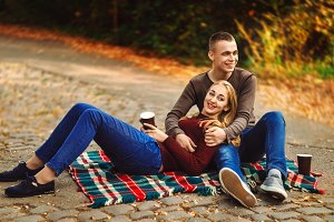 the girl is lying with the guy in his arms. they are sitting on a blanket. drink a hot drink. open air. love
