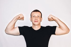 portrait of a man. the guy shows his biceps. White background. black T-shirt. health and sport.