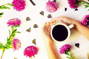a cup of hot coffee. hands in sequins. diamonds and flowers. background and texture.
