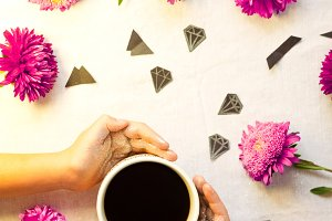 hands in sequins. a cup of hot coffee. asters and diamonds on a white background. Delicate background. women's Day
