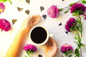 hot coffee. hands holding a mug. flowers and diamonds. view from above.