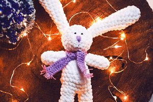 soft knitted rabbit with long ears. handmade. new year and holidays. gift. lights