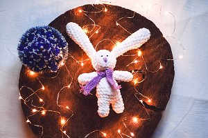 soft toy for a gift for the new year. the lights glow. view from above. wooden background