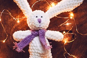 a handmade toy. knitted toy knitting needles. a hare for a gift. new Year. garlands shine. wooden background