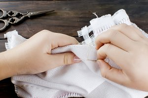 Little girl's hands embroiding cross