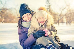 Mother and daughter playing at winter day