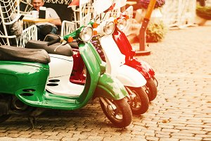 the flag of Italy. three retro scooters on the streets of the city.