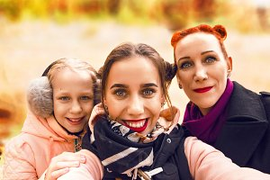 a happy family. Sisters and Mom make selfies. are similar to each other.