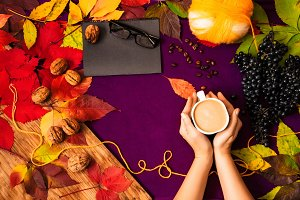 hands holding a cup of cappuccino. autumn harvest. colorful leaves. notebook