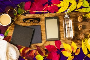 view from above. leaves of different colors. autumn mood, hot coffee, gadgets, clean water in my bottle