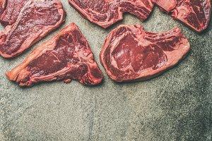 Porterhouse, t-bone and rib-eye steaks over grey background