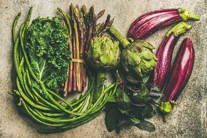 Flat-lay of fresh green and purple vegetables over concrete background