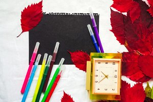 the template is clean. black sheet of paper. felt pens of different colors. leaves of autumn. alarm clock