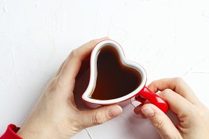 Female hand holding cup of tea