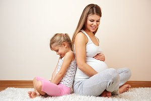Little girl and pregnant mom at home