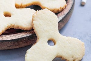 Homemade shortbread cookies made in trendy spinner toy form and a glass of milk, square