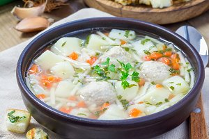 Homemade soup with meatballs and vegetables, served with cheese garlic parsley croutons, square