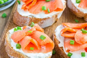 Sandwich with smoked salmon and cream cheese on wooden board, square format