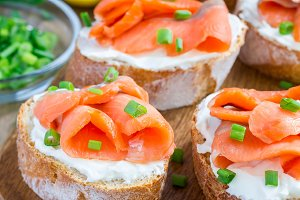 Sandwich with smoked salmon and cream cheese on wooden board, square