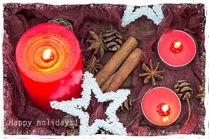 Christmas composition with with red candles, stars, winter spices and cones. Snowy frame and happy holidays text.