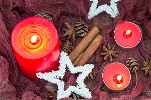 Christmas composition with with red candles, star decorations, winter spices and cones