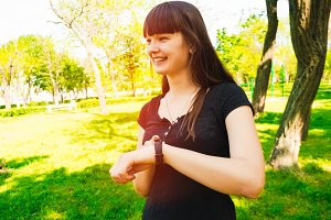 girl with a smile on her face. looks at his watch. pedometer. new technologies