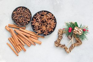 Different kinds of aromatic winter spices in bowls, christmas decoration on gray concrete background, top view, horizontal