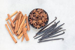 Different kinds of aromatic winter spices on gray concrete background, top view, horizontal