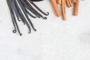 Different kinds of aromatic winter spices on gray concrete background, top view, copy space, vertical