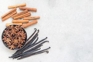 Different kinds of aromatic winter spices on gray concrete background, top view, copy space, horizontal