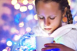 the girl is holding a cup with a hot drink. Christmas mood. bokeh from the garlands. hot steam. portrait