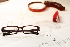 project of work production. industry. office glasses, magnifier, stapler. blueprints