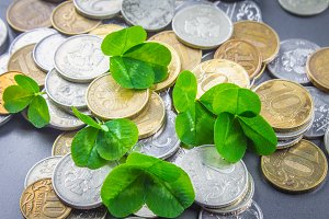 Scattered Russian coins on a gray background with leaves of clover. Good luck, St. Patrick's day.