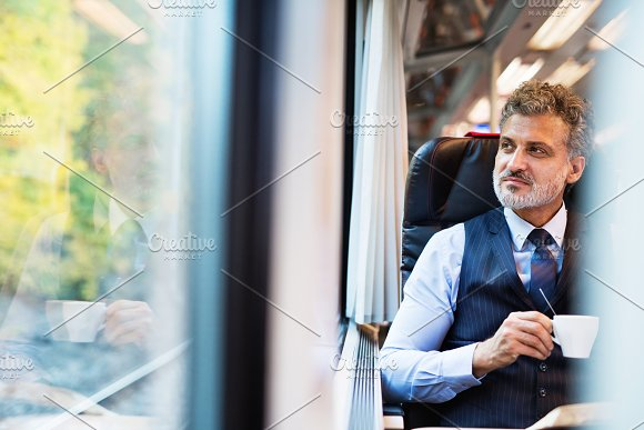 Mature businessman with coffee travelling by train.