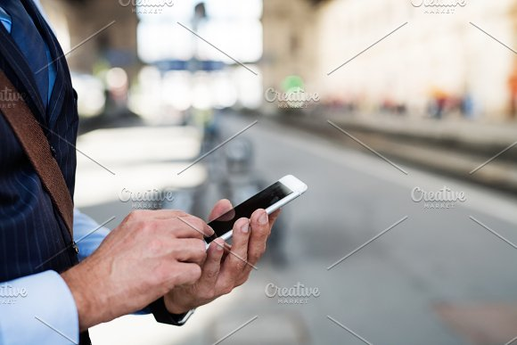 Mature businessman with a smartphone in a city. in Graphics